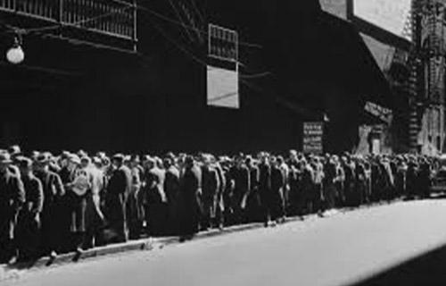 Foto em preto e branco de um cenário de 1929, em que mostra uma longa fila de pessoas, todas à calçada da rua.