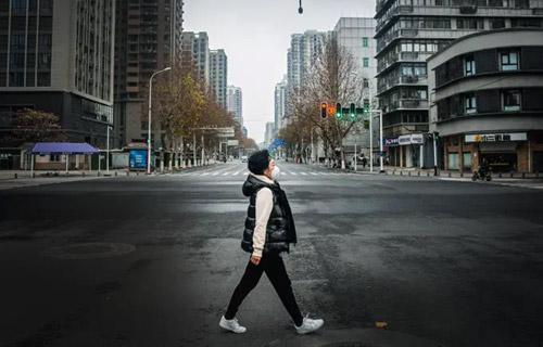 Foto colorida de um cenário atual, 2020, de uma mulher caminhando sozinha em uma rua completamente deserta da cidade.